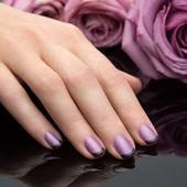 Beautiful manicure, polish is a violet color. Flower background. — Zdjęcie stockowe