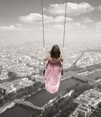 Young woman on a swing on the Paris town backround — Stock Photo