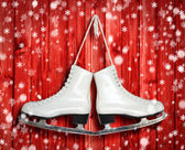 Pair of White Ice Skates on red wooden backround — Stock Photo
