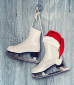 Pair of White Ice Skates and Santa Claus hat - backround on vint — Stock Photo