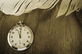 Pocket Watch and Feather on Wood — Stock Photo