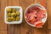 Typical Spanish tapas: serrano ham and green olives — Stock Photo