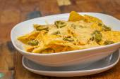 Nachos with cheese and jalapenos in a white bowl — Stok fotoğraf