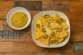 Nachos with cheese and jalapenos in a white bowl and fresh guaca — Stok fotoğraf