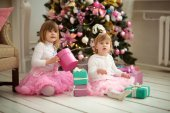Sisters with gifts by the Christmas tree with pink toys — Stock Photo