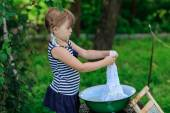 Little helper girl washes clothes in a basin outdoors — Stock Photo