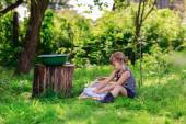 Little helper girl washes clothes using the washboard outdoors — Stock Photo