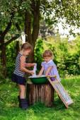 Little helper girls sisters washes clothes using the washboard o — Stock Photo