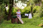 Little helper girl washes clothes   in a basin outside — Stock Photo
