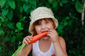 Girl gnaws carrot — Stock Photo