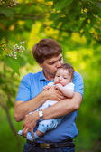 Dad with a baby boy in his arms, close-up, summer — Stock Photo