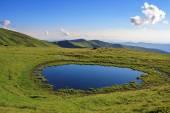 Mountain lake on slopes — Stock Photo