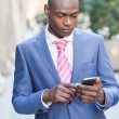 Black businessman reading his smartphone in urban background — Stock Photo #63196607