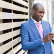 Black man looking at his tablet computer in urban background — Stock Photo #63196649