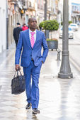 Black businessman walking on the street with a modern briefcase — Stock fotografie