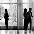 Silhouettes of businesspeople interacting background business ce — Stock Photo #69635559