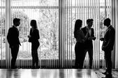 Silhouettes of businesspeople interacting background business ce — Stock Photo