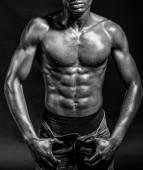 Athletic black man on black background — Stock Photo