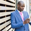 Black man wearing suit looking at his tablet computer — Stock Photo #75973577
