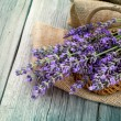 Lavender flowers in a basket with burlap on the wooden backgroun — Stock Photo #52132701