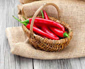 Red chili pepper in a wicker basket with burlap on the wooden ba — Stock Photo