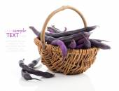 Red bean pods in wicker basket over white background — Stock Photo