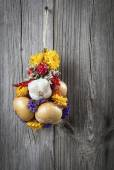 Braided bunch with onions, garlic and flowers, on wooden backgro — Zdjęcie stockowe