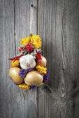 Braided bunch with onions, garlic and flowers, on wooden backgro — ストック写真
