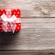Red gift box, polka dots, on wood background — Stock Photo #54371191