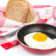 Fried egg in a frying pan, over white background — Stock Photo #55268093