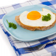 Fried egg in blue plate with fork, over white background — Stock Photo #55268275