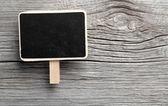 Vintage slate chalk board hanging on wooden background — Stock Photo