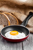 Fried egg in a frying pan, on an old wooden table — Stock Photo