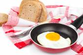 Fried egg in a frying pan, over white background — Photo