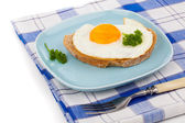 Fried egg in blue plate with fork, over white background — Photo