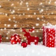 Red gift for christmas on a wooden background with snow — Zdjęcie stockowe #55272699