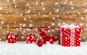 Red gift for christmas on a wooden background with snow  — Stock Photo