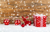 Red gift for christmas on a wooden background with snow  — 图库照片