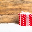 Red gift for christmas on a wooden background with snow — Stock Photo #56149009