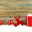 Red gift for christmas on a wooden background with snow — Stock Photo #56169511