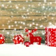 Red gift for christmas on a wooden background with snow — Stock Photo #57642875