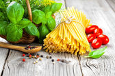 Fresh pasta and italian ingredients on wooden table — Stock Photo