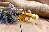 Essential oil botle and lavender flowers, on wooden background. — Stock Photo