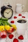 Cup of coffee, hours and tulips — Stock Photo
