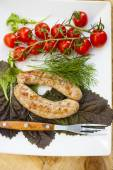 Sausage a grill, tomatoes and greens  — Stock Photo