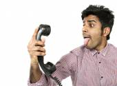 Young man struggling with a crazy telephone — Stock Photo