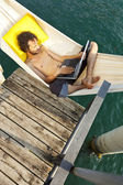 Young man on the dock of Lake — Stockfoto