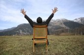 Man sits on a chair into the wild — Stock Photo