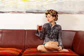 Girl drinking a drink on the couch — Stock Photo
