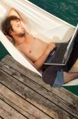 Young man with laptop on the dock — Stock Photo